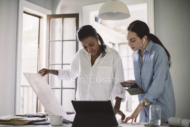 Diseñadoras mujeres debatiendo mientras trabajan en la mesa en la oficina de casa - foto de stock