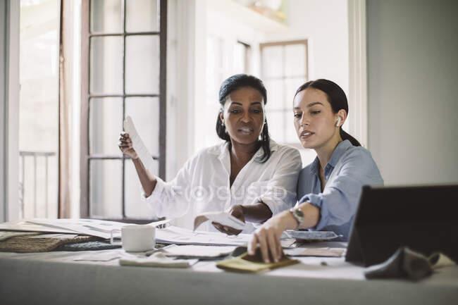 Femmes architectes discutant tout en travaillant à table au bureau à domicile — Photo de stock