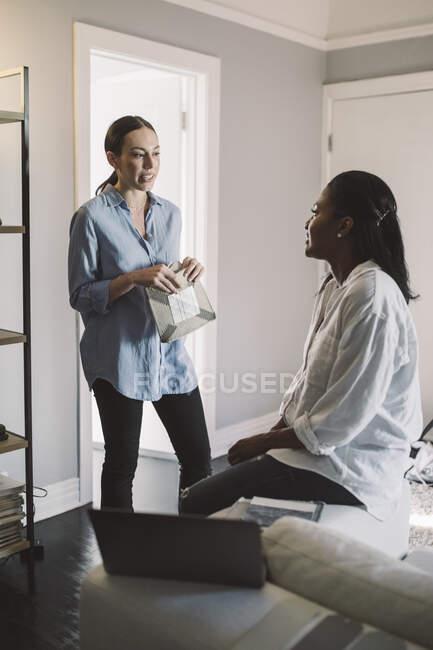 Жінки - підприємці обговорюють справи у вітальні вдома. — стокове фото