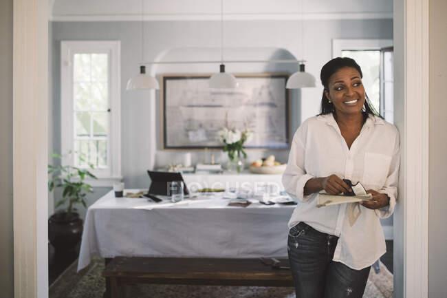 Усміхаючись, жінка - професіонал відводить погляд убік, стоячи вдома. — стокове фото