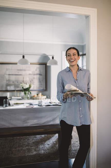 Happy design professionnel avec papier et tissu swatch debout dans le bureau à la maison — Photo de stock