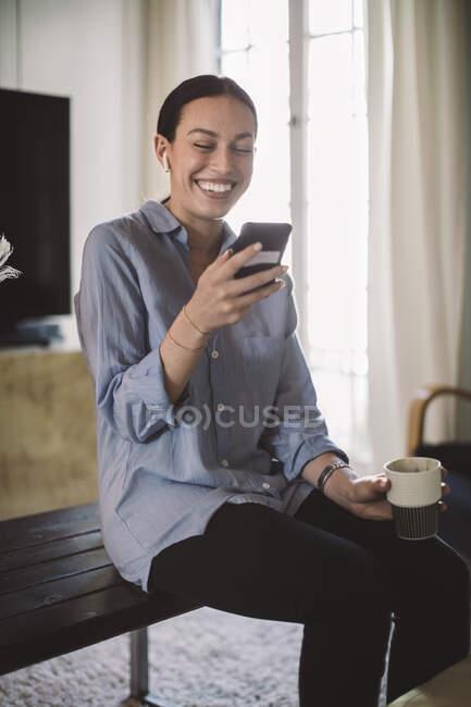 Feliz profesional con taza usando teléfono móvil mientras está sentado en la mesa en la oficina de casa. - foto de stock
