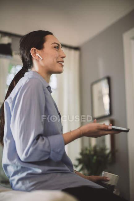 Smiling profesional con taza y teléfono móvil hablando a través de auriculares en la oficina de casa. - foto de stock