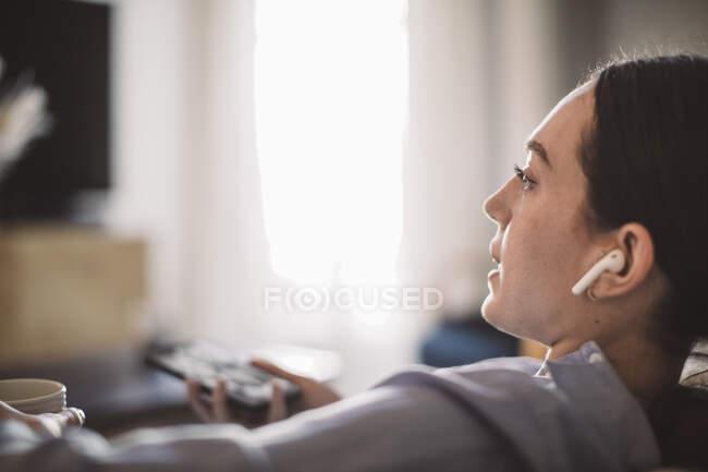 Design profissional com bebida e telefone inteligente falando através de fones de ouvido em casa escritório — Fotografia de Stock