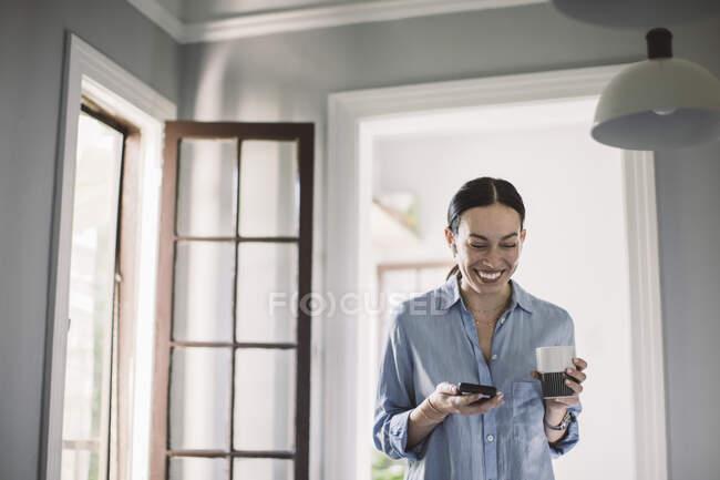 Profesional de diseño feliz con bebida y teléfono inteligente de pie en la oficina de casa. - foto de stock