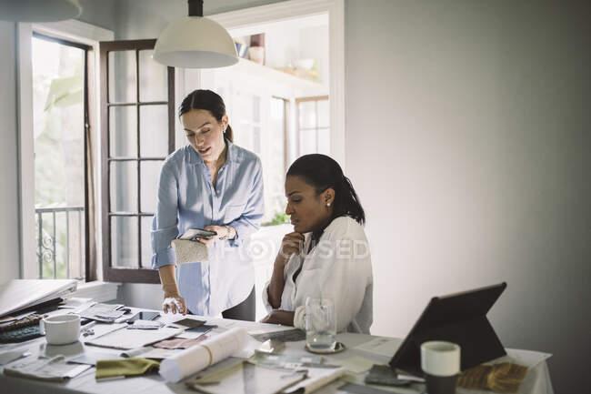 Жіночі архітектори обговорюють тканинні годинники під час роботи за столом у домашньому офісі. — стокове фото