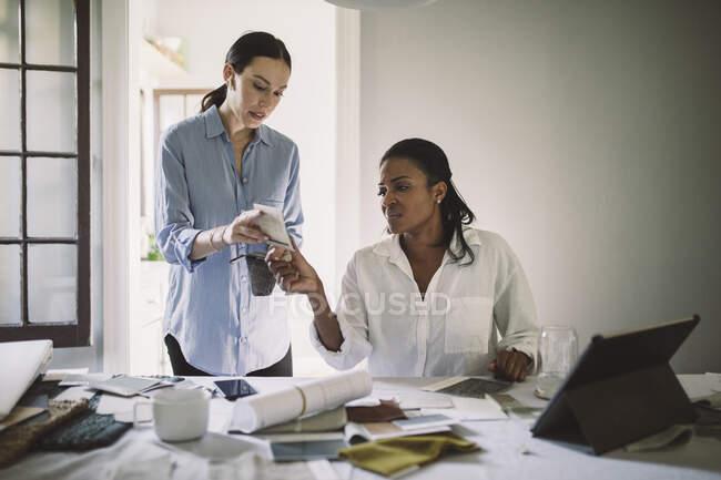 Designerinnen diskutieren über Stoffmuster bei der Arbeit am Tisch im Homeoffice — Stockfoto