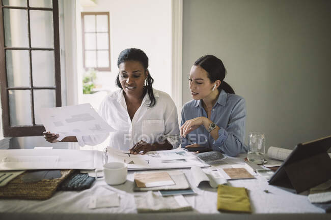 Female architects working while sitting at table in home office — Stock Photo