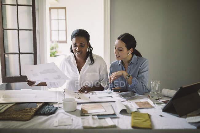 Arquitectos femeninas que trabajan sentadas a la mesa en la oficina de casa - foto de stock