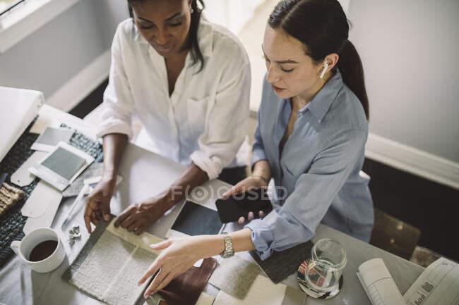 Vista de gran angular de las diseñadoras que trabajan mientras están sentadas en la mesa en la oficina de casa. - foto de stock