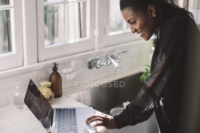 Femme souriante professionnelle utilisant un ordinateur portable tout en restant debout au bureau à la maison — Photo de stock