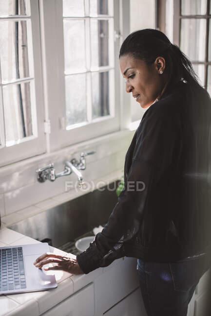 Side view of female professional using laptop while standing by sink at home office — Stock Photo