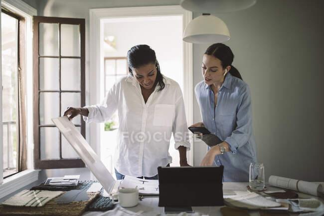 Architectes féminines travaillant à table au bureau à domicile — Photo de stock