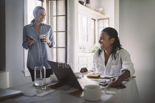 Cheerful female entrepreneurs in living room at home office — Stock Photo