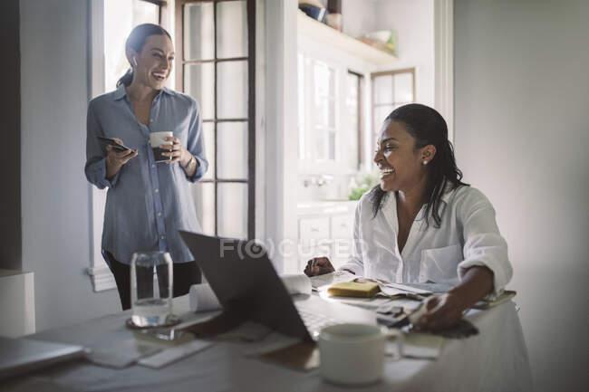 Empreendedoras alegres na sala de estar em casa escritório — Fotografia de Stock