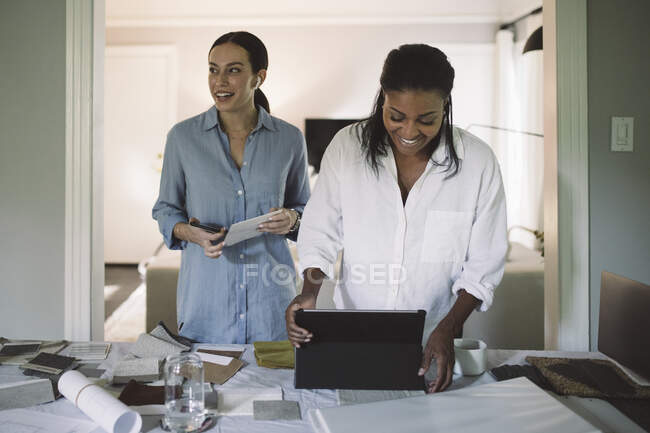 Smiling entrepreneurs working while standing by table in living room at home office — Stock Photo