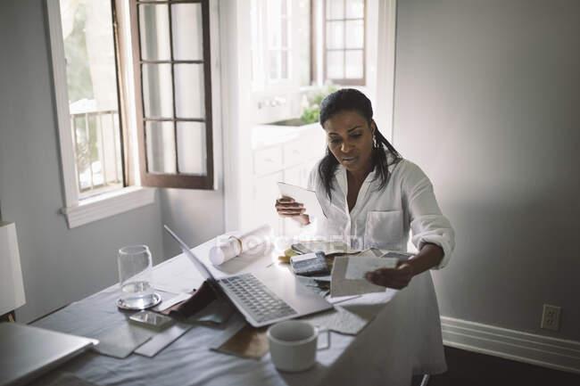Mujeres empresarias que trabajan mientras están sentadas a la mesa de comedor en la oficina de casa - foto de stock