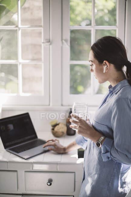 Vista lateral do profissional do sexo feminino usando laptop no balcão enquanto bebe água em casa escritório — Fotografia de Stock