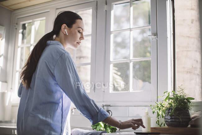Vista lateral da empresária usando telefone inteligente no balcão de cozinha em casa escritório — Fotografia de Stock