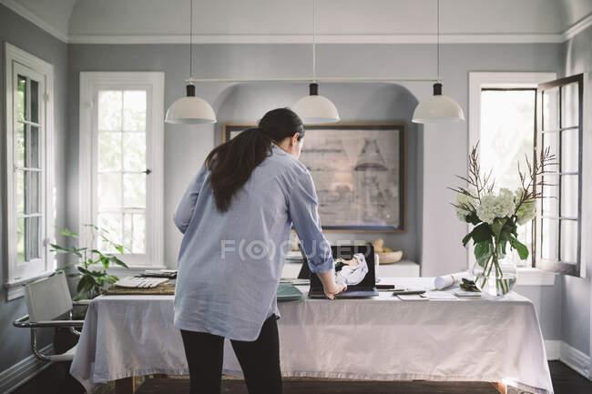 Vue arrière du professionnel féminin utilisant un ordinateur portable dans le salon au bureau à la maison — Photo de stock
