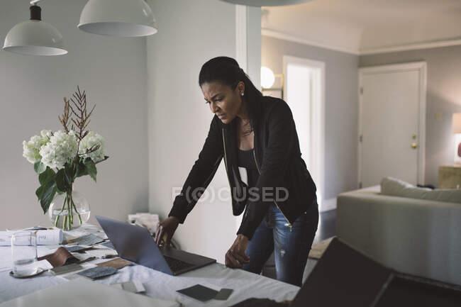 Стурбована бізнес-леді, яка дивиться на ноутбук, стоячи за обіднім столом у себе вдома. — стокове фото