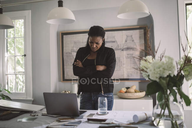 Contemplating business woman with arms crossed looking at laptop while standing at dining table at home office. - foto de stock
