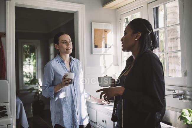 Femmes designers discutant tout en restant près du comptoir de cuisine à la maison — Photo de stock