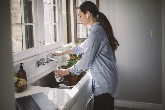 Бічний вид на жінку, яка заповнює воду в банці в кухонному раковині. — стокове фото