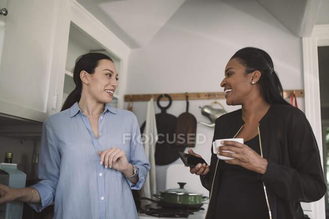 Усміхаючись, жінки - дизайнерки обговорюють справи на кухні в домашньому офісі. — стокове фото