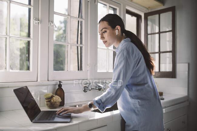 Vista lateral do profissional do sexo feminino usando laptop no balcão em casa escritório — Fotografia de Stock