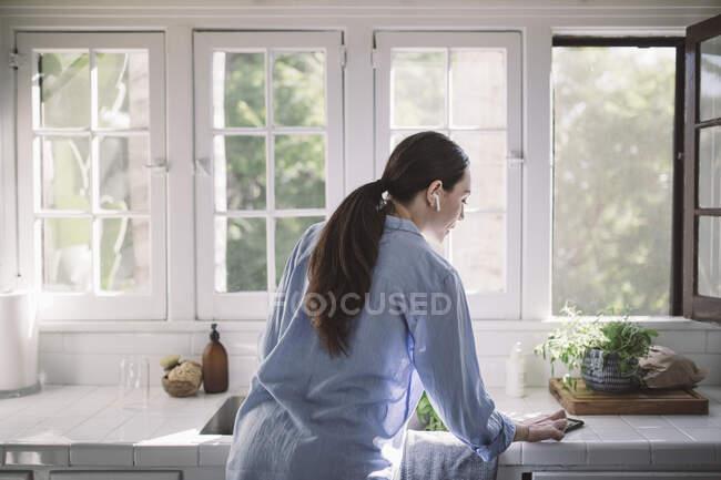 Vista trasera de la mujer de negocios utilizando el teléfono inteligente en el mostrador de la cocina en la oficina en casa - foto de stock