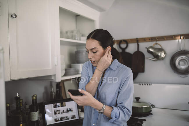 Female design professional wearing in-ear headphones at home office — Stock Photo