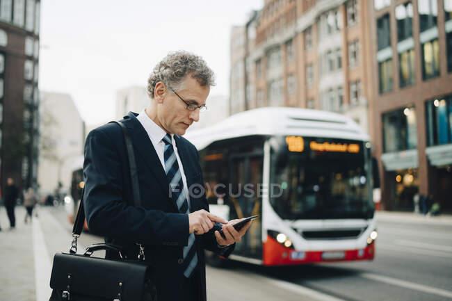 Maduro empresário usando inteligente telefone enquanto está em pé na cidade — Fotografia de Stock