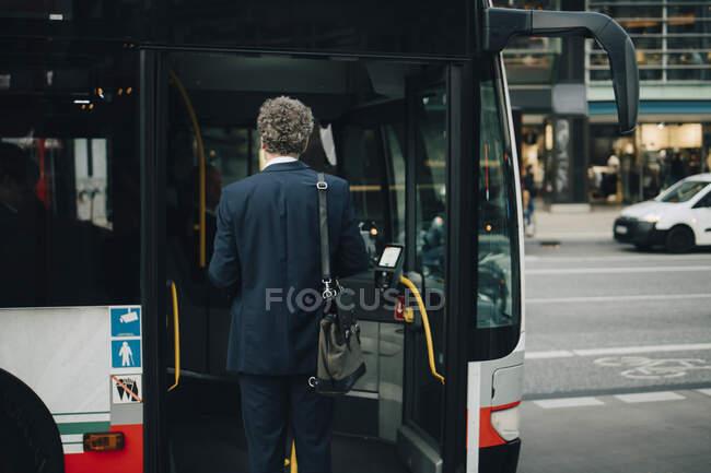 Передній вигляд чоловіка - підприємця, який сідає в автобус під час ділової поїздки в місто. — стокове фото