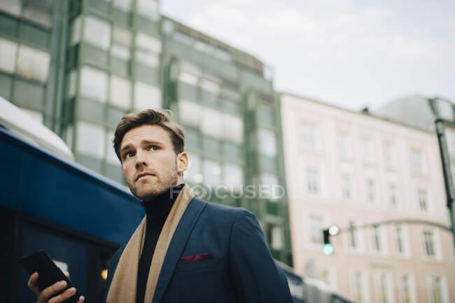 Vista basso angolo di uomo d'affari guardando lontano mentre in piedi contro l'autobus in città — Foto stock