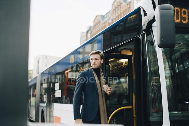 Бізнесмен з обгорнутим бутербродом, який відвів погляд, стоячи навпроти автобуса в місті. — стокове фото
