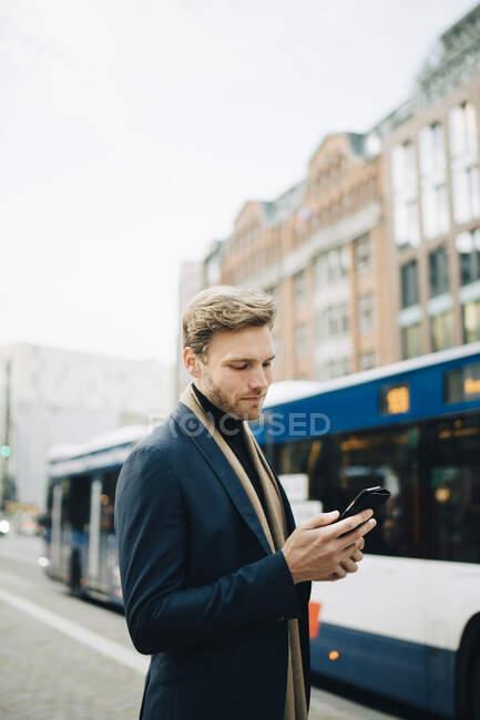 Empresarios confiados navegando por la red a través de teléfonos inteligentes mientras se alojan en la ciudad. - foto de stock