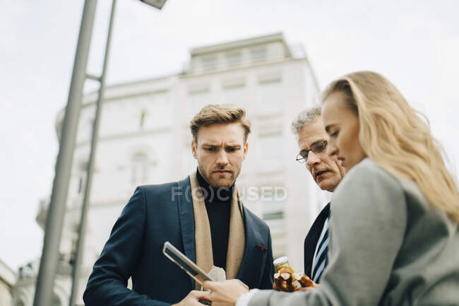 Low angle view of worried business executives looking at mobile phone while standing in city — Stock Photo