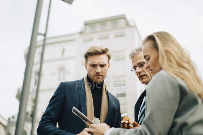 Vista de bajo ángulo de los empresarios preocupados mirando al teléfono móvil mientras se alojan en la ciudad. - foto de stock
