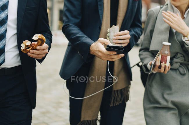 Midsection of business professionals holding pretzel and drink while using smart phone in city. - foto de stock