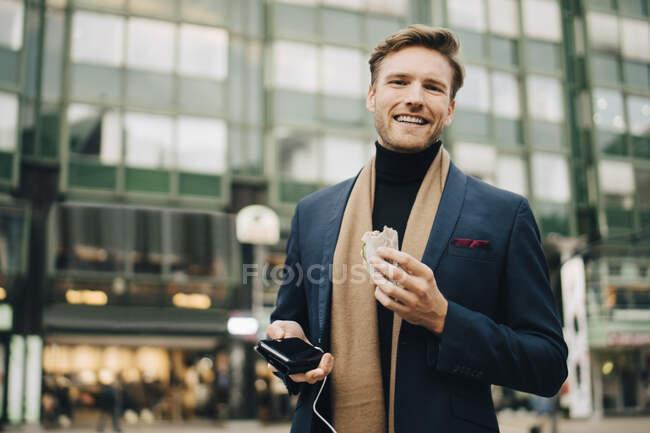 Ritratto di uomo d'affari sorridente con panino avvolgente in piedi in città — Foto stock