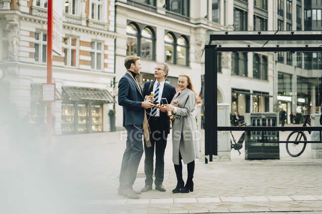 Des collègues souriants, hommes et femmes, parlent en ville — Photo de stock
