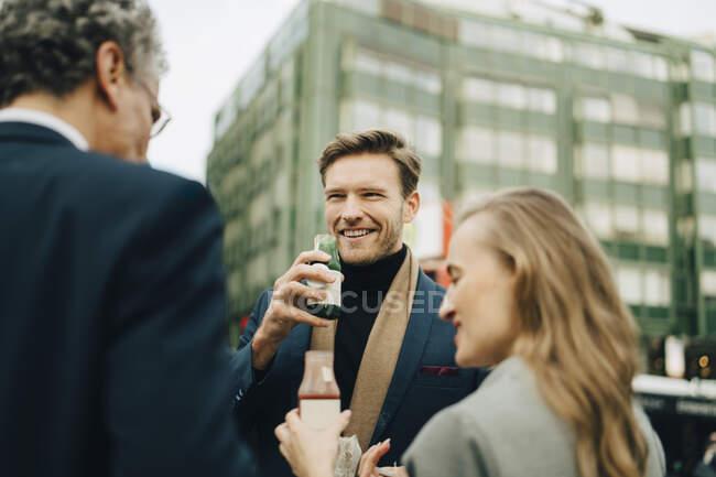 Sourire entrepreneur masculin avec boisson en regardant des collègues dans la ville — Photo de stock