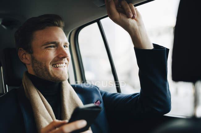 Uomo d'affari sorridente con il telefono che distoglie lo sguardo mentre si siede in taxi — Foto stock