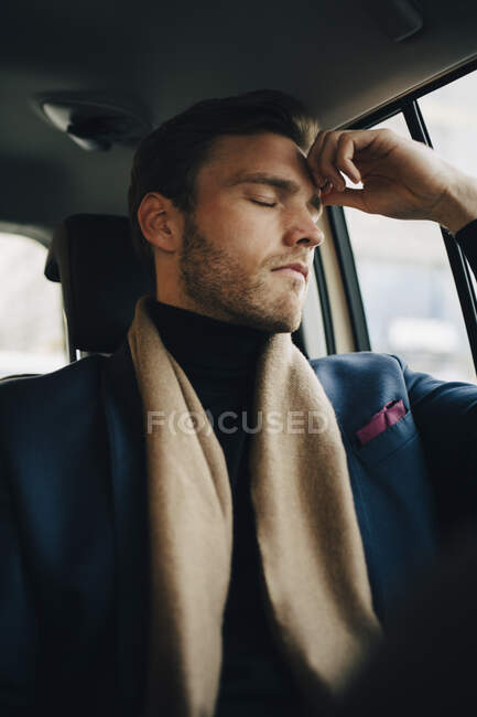 Sad businessman in suit with eyes closed sitting in taxi — Stock Photo