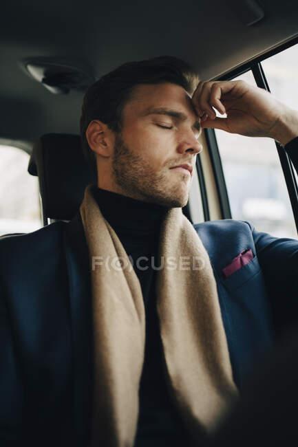 Triste empresário em terno com os olhos fechados sentado no táxi — Fotografia de Stock