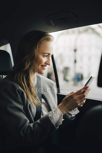 Smiling entrepreneur using smart phone while sitting in taxi — Stock Photo