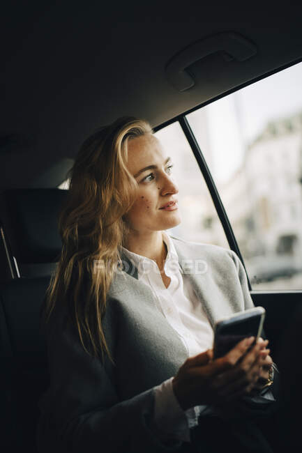 Confident female entrepreneur with smart phone looking through window while sitting in taxi — Stock Photo