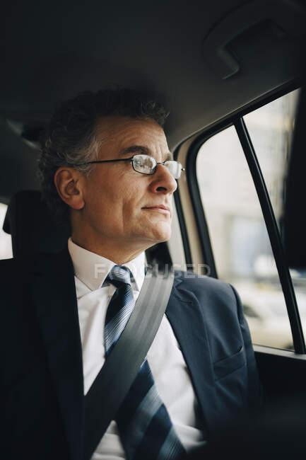 Entrepreneur regardant par la fenêtre tout en étant assis en taxi — Photo de stock