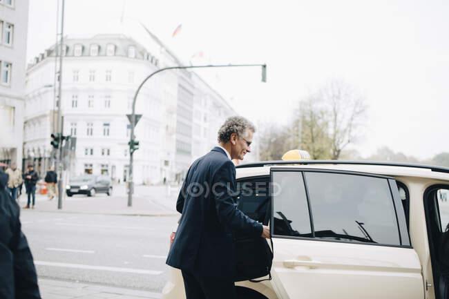 Maduro empresário por táxi porta no cidade — Fotografia de Stock